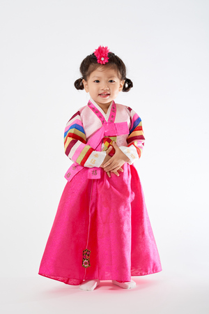 Smile Korean little girl wearing a Traditional Hanbok dress in white background. The characters on the dress means happiness and healthy.