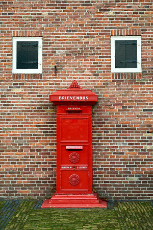 Ancient post box in Amsterdam, Netherlands. The Dutch on the photo means mail box and letters. Standard-Bild