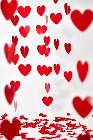 Valentine's Day red hearts on white background with rose pedals on the floor Standard-Bild