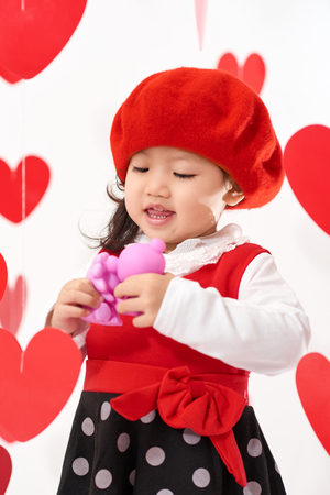 Cute Asian baby girl with hearts and rose pedals on Valentine's Day