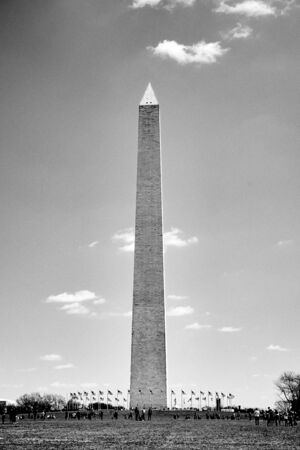 Washington DC, USA - April 2018: Close up of the Washington Monument surrounded by American flags and visitors in black and white.