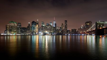 Great night view of the famous skyline of Manhattan downtown district with many skyscrapers and Brooklyn Bridge, whose lights reflects in the water.