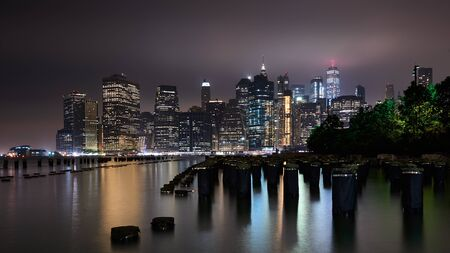 Great night view of the famous skyline of Manhattan downtown district with many skyscrapers, whose lights reflects in the water.