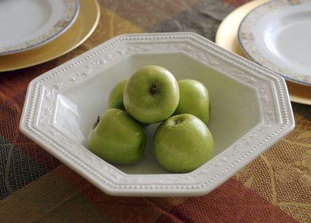 presentaion: A bowl of apples in the center of a dinner table.