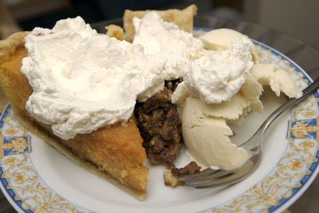 Slices of homemade pie on a plate covered with ice cream.