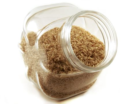 A jar of dried brown rice shot isolated against a white background. Stock Photo