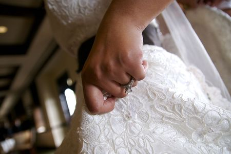 A close shot of a brides hand lifting her dress slightly. Stock Photo