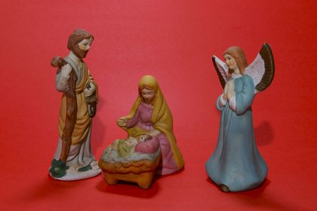 A ceramic depiction of the Nativity isolated against a red background.
