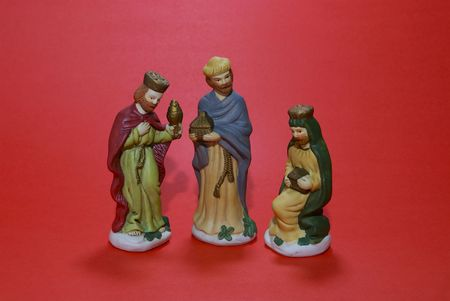 A ceramic depiction of the three wise men isolated against a red background.