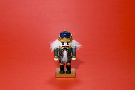A green Christmas Nutcracker isolated against a red background.