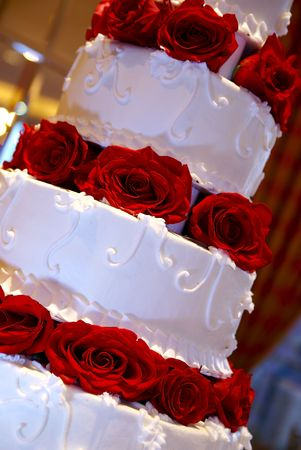 A Large Bridal cake with layers of red roses. Stock Photo
