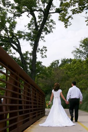 A young married couple walking across a small bridge. Stock Photo