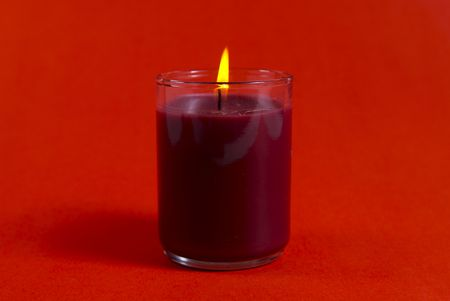 A small Christmas candle shot against a red background. Stock Photo