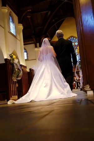the happy bride: A bride and her father beginning their walk down the aisle. Stock Photo