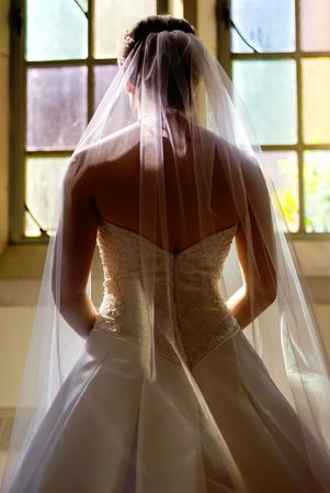 A bride looking out the window of her dressing room before her wedding.