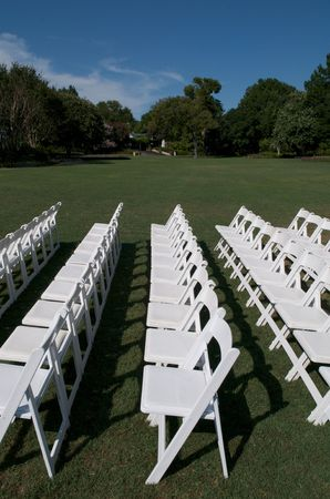 Rows of white chairs under blue sky. Stock Photo