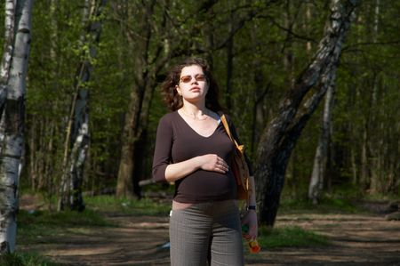 The pregnant woman walking in a forest