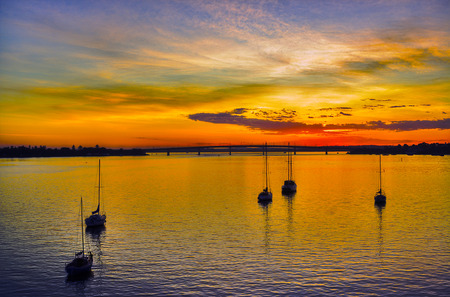 early morning golden sunrise over botany bay sydney with, boats in the forground, dramatic, sky,