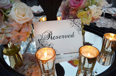 Reservation sign with wedding bouquet and glasses on table