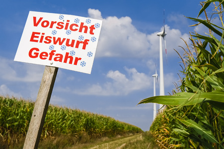 cautions: Danger sign in front of wind turbines near, Wustermark, Germany Stock Photo