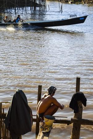cowering: Bather at canal to Inle Lake, Nyaung Shwe, Myanmar, Asia