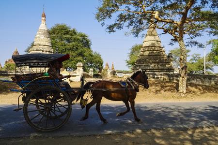 buddhismus: Horse-drawn carriage on road near Nyaung U, Bagan, Myanmar