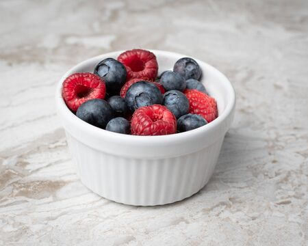 Blueberries and raspberries in a white bowl on a grey and white marble background