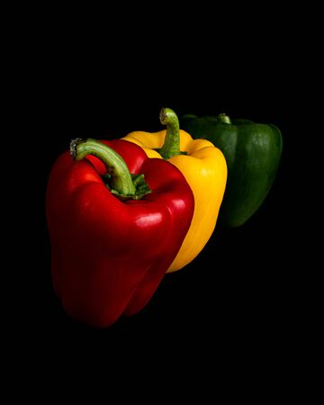 Red, Yellow and Green Bell Peppers Isolated on a Black Background