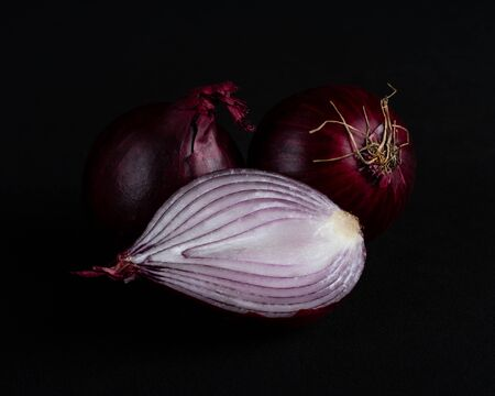 Half a red onion and two red onions isolated on a black background