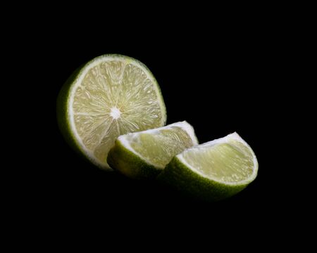 Half a Lime and Slices of Lime Isolated on a Black Background