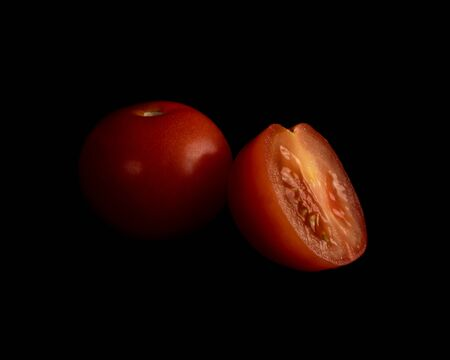 Half a red tomato and a whole red tomato isolated on a black background