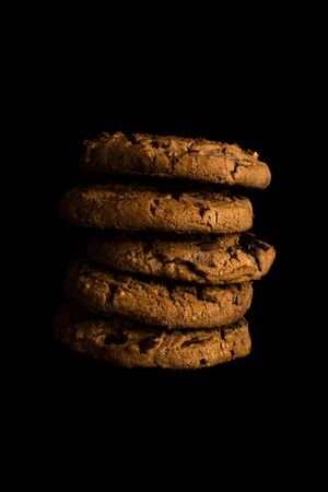 Stack of chocolate chip cookies isolated on a black background