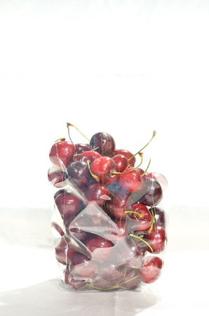 a lot of cherrys in plastic bag isolated on white background photo