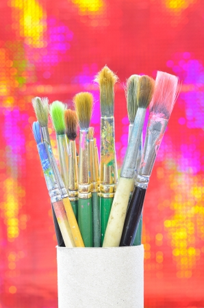 bakground: paint brushes in paper box on red bakground
