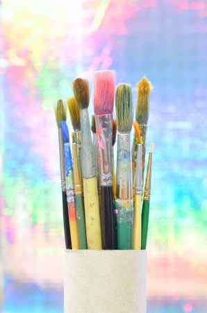 bakground: paint brushes in paper box on light bakground