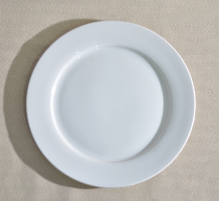 an empty circle white dish on a table linen Stock Photo