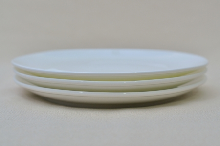 overlap: an empty circle white dish overlap on a table linen Stock Photo