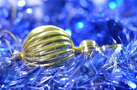 one gold christmas ornament on the blue shiny chain Stock Photo