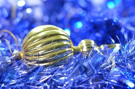 una de oro adorno de Navidad en la cadena azul brillante