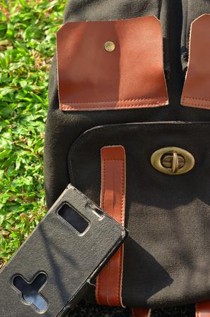 mochila de viaje: mochila de viaje negro y el tel�fono inteligente en la hierba