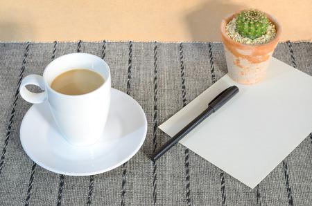 carta e penna: tazza di caff� con carta, penna e cactus su tovaglietta