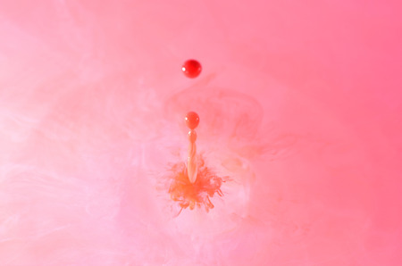 red water: red water drop with ripple on pink background Stock Photo
