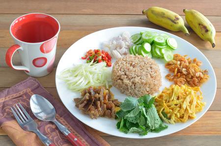pl�tano frito arroz con pasta de camarones en un plato blanco con vidrio y cultivada sobre tabla de madera Foto de archivo