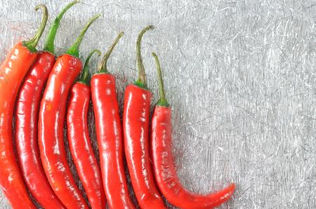 table linen: red goat horn pepper on silver table linen