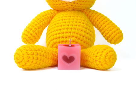scented candle: square pink scented candle and yellow knitting bear doll on white background