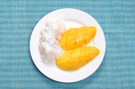thailand culture: mango sticky rice with coconut milk on white dish