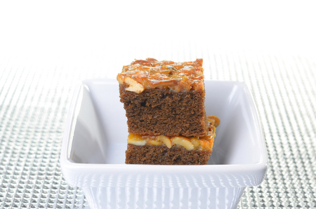 savour: toffee cake in white square bowl on silver napery Stock Photo