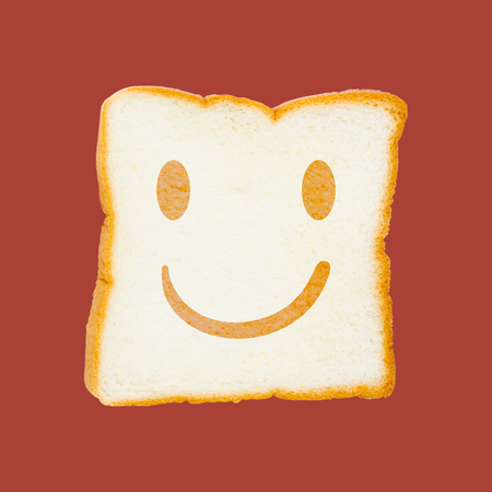 the smile face slice breads on red brown Stock Photo