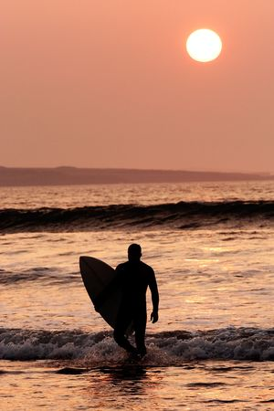 surfboard fin: Surfer exiting the water. Silhouette of man carrying surfboard