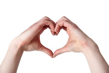 cuore in mano: Due mani clasped insieme facendo una forma di cuore  Archivio Fotografico
